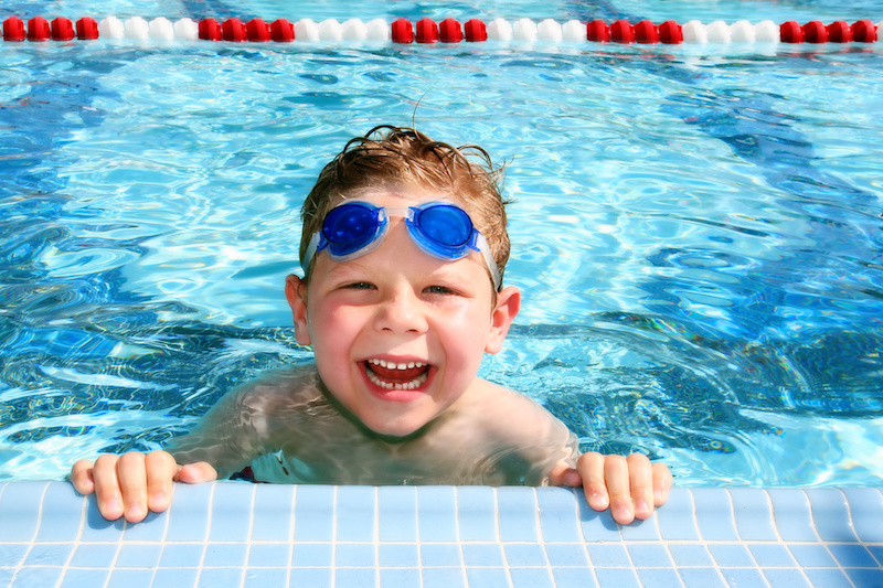 Summer safety; Smiling six year old boy in a sunny swimming pool