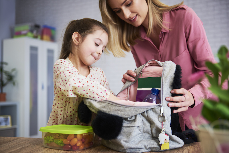 Young mum and daughter packing backpack for the school; back to school tips for parents