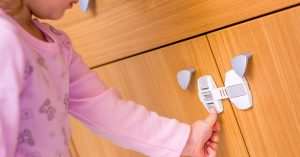 Baby girl trying to open the kitchen cabinet – baby proofing the door; blog: How to Babyproof Your Home