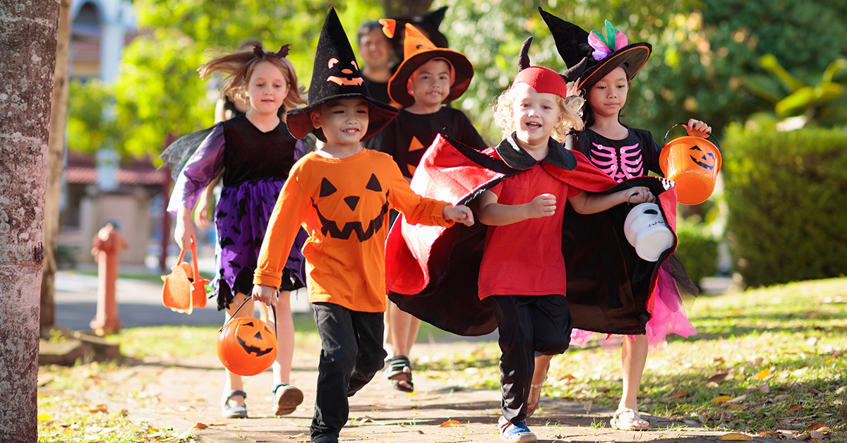 Child in Halloween costume. Mixed race Asian and Caucasian kids and parents trick or treat on street. Little boy and girl with pumpkin lantern and candy bucket. Baby in witch hat. Autumn holiday fun; blog: dos and don'ts of trick or treating
