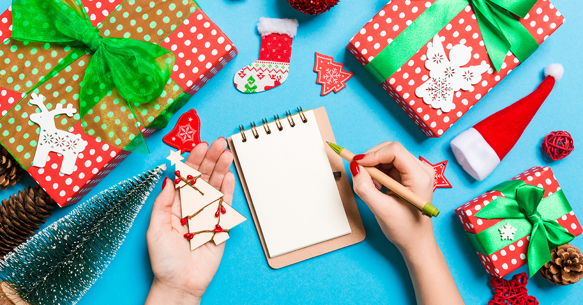 Top view of female hand making some notes in noteebok on blue background. New Year decorations and toys. Christmas time concept; blog: 14 Non-Toy Gift Ideas for Kids
