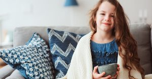 child girl drinking hot tea to recover from flu. Healing kids and protect immunity from seasonal virus, health concept; blog: keep kids healthy this winter