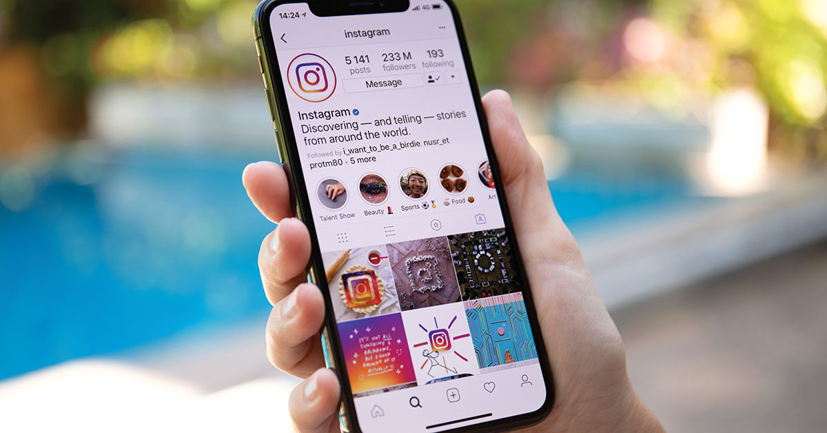Woman hand holding iPhone X with social networking service Instagram on the screen. iPhone 10 was created and developed by the Apple inc.; instagram accounts for parents to follow