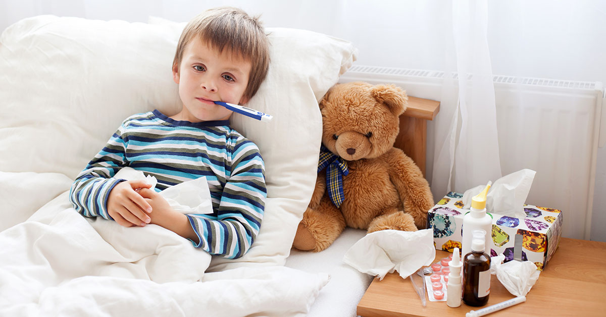 Sick child boy lying in bed with a fever, resting at home; blog: Sick Days: When to Keep Your Child Home From School