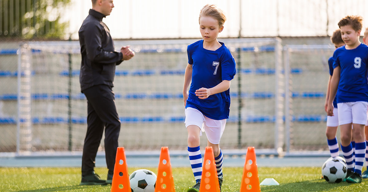 Young Happy Blonde Soccer Player Running with Ball on Training. Coach of Youth Football Team Explaining Drill Exercise in the Background. Caucasian Soccer Players on Practice Session; blog: Sports Physicals for Kids: What to Expect