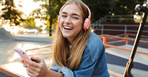 Image of a laughing cheery smiling young teenage girl outside in park listening music with headphones holding mobile phone showing tongue; blog: stages of adolescence