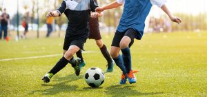 Two soccer players running and kicking a soccer ball. Legs of two young football players on a match. European football youth player legs in action; blog: Preventing and Treating Common Kids Sports Injuries