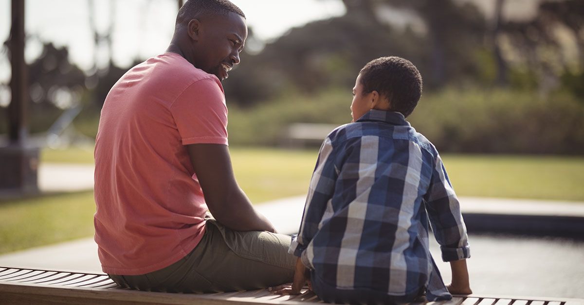 Father talking to son near pool side; blog: 8 Tips for Talking to Kids About Drugs