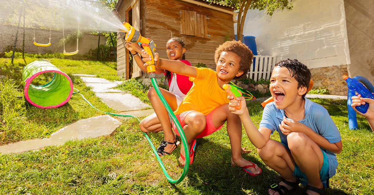 Group of happy kids scram smile squat and shoot with water guns, garden hose playing game on backyard; blog: 8 Healthy Activities for Kids to Do While School's Out