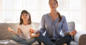 Calm smiling mother with cute little daughter doing yoga exercise at home, pretty girl and attractive mum with closed eyes sitting in lotus pose on couch, relaxing together, family exercise; blog: 9 Mental Health Tips for Kids in Stressful Times