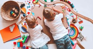 Kids draw and make crafts. Children with educational toys and school supplies for creativity. Background for preschool and kindergarten or art classes. Boy and girl play at home or daycare; blog: 11 Ways to Entertain Kids During a Pandemic