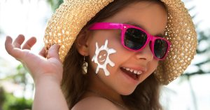 Happy child in glasses with sunscreen on the face; blog: 5 Sun Safety Tips for Kids