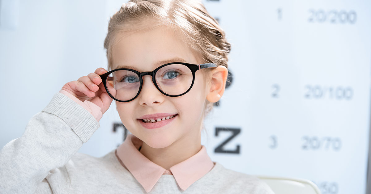 adorable smiling child looking at camera in glasses at oculist consulting room; blog: Does Your Child Need Glasses?
