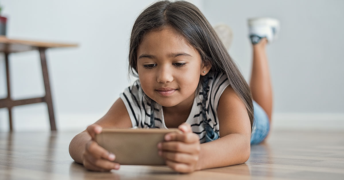 Little asian girl lying on floor using mobile phone to play. Multiethnic female child watching cartoon on smartphone at home. Childhood and moder technology concept; blog: 8 Tips for Limiting Screen Time for Kids