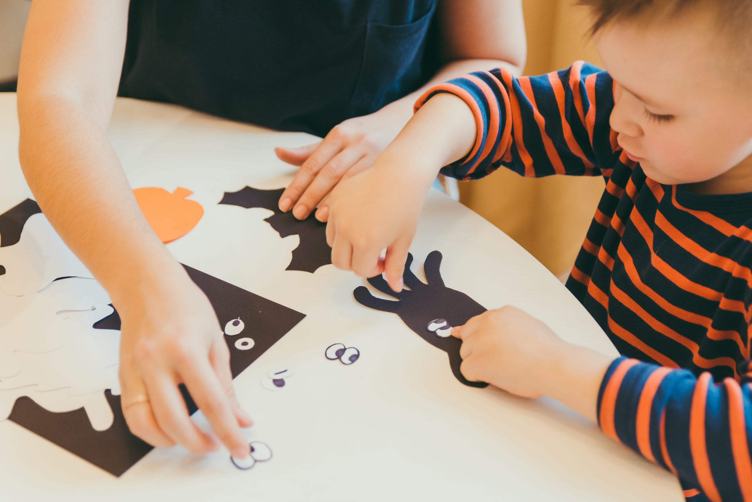 young mother with toddler son making craft spiders for halloween holiday family time