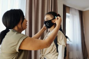 mom putting face mask on child