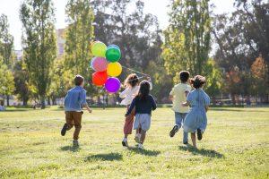 children running with balloons
