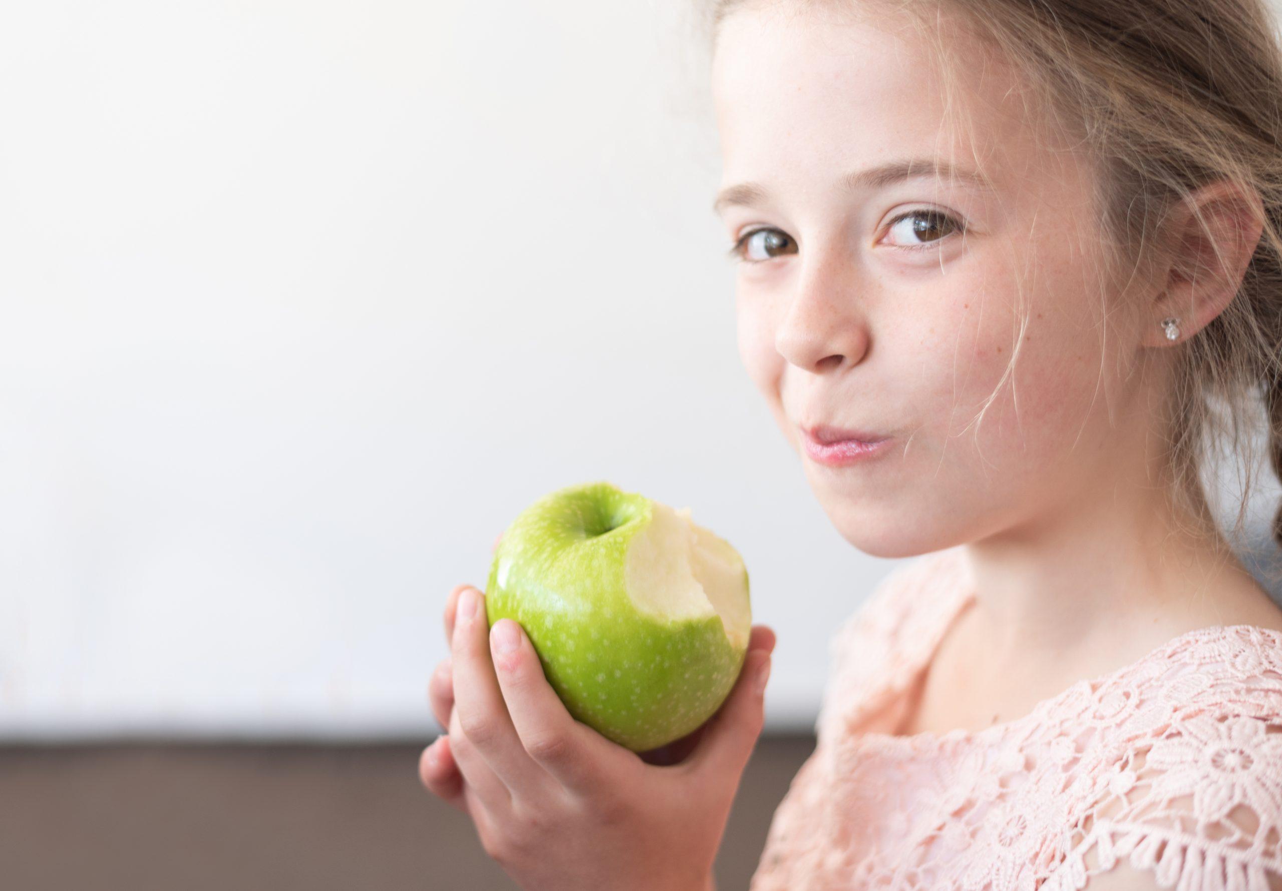 little girl eating apple national health month