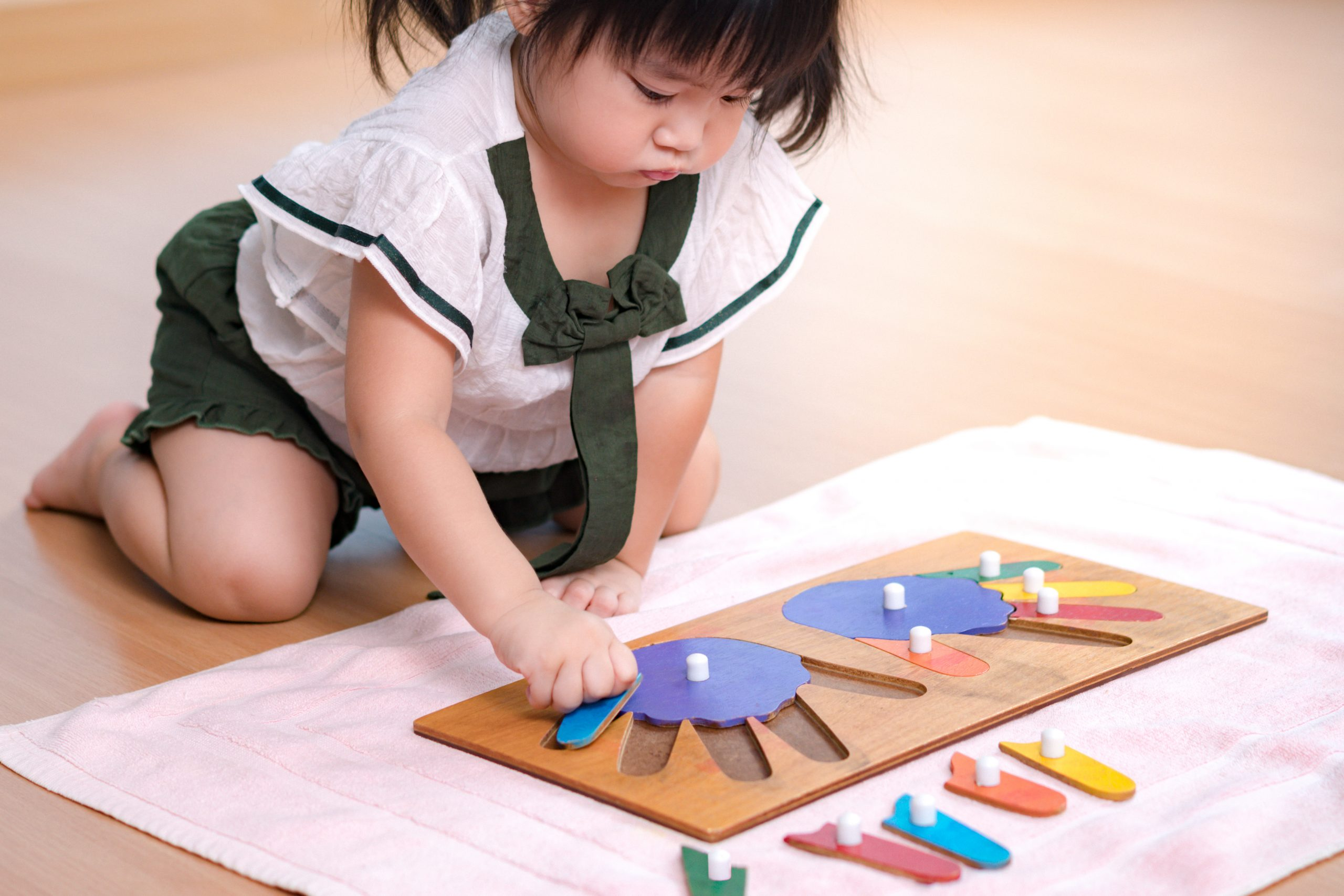 preschool little girl (2-3 years) in Montessori classroom engaged sensory wooden puzzle activity. 10 fingers, Fine motor skills, Montessori method, Child development, Early education
