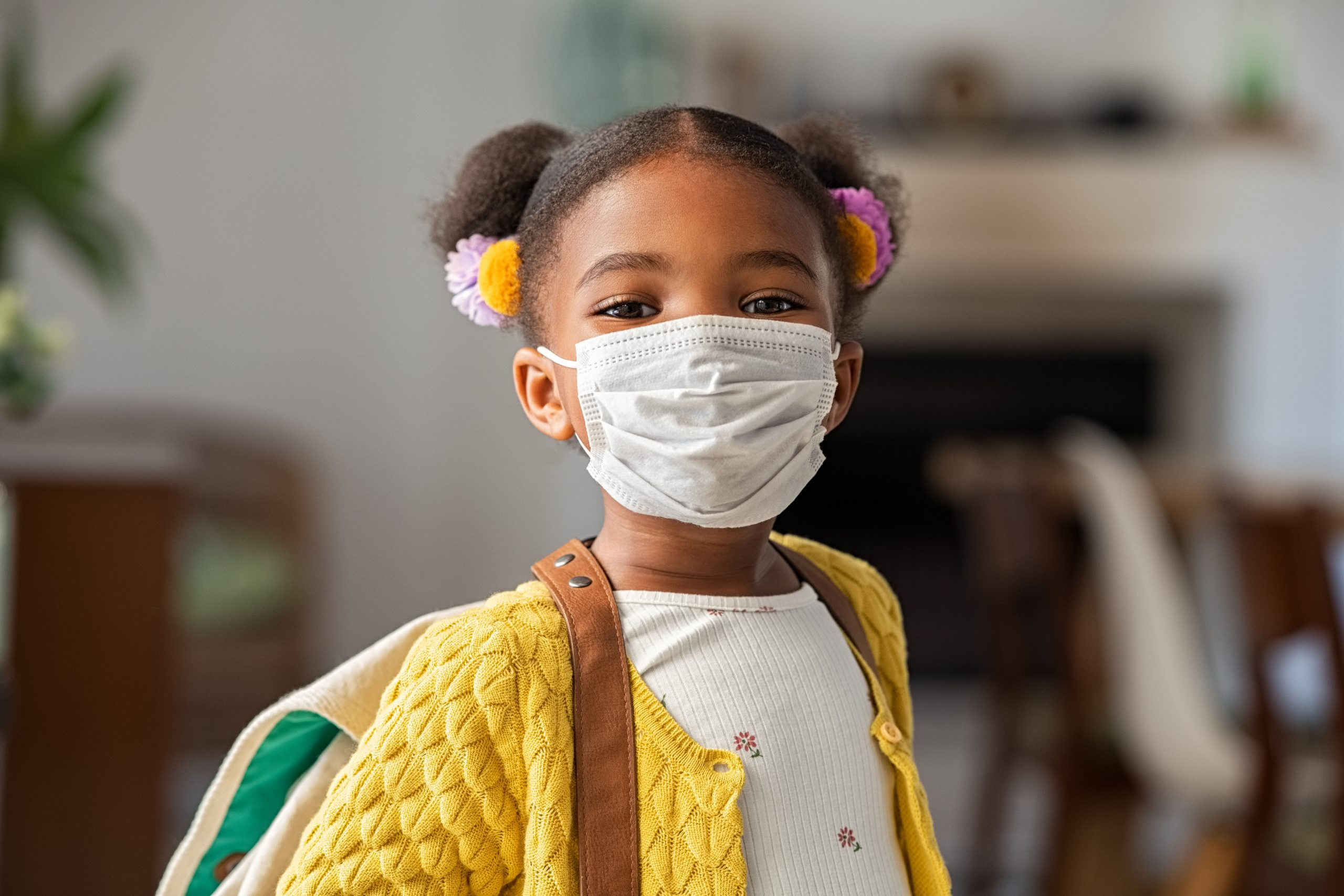 Portrait of black little girl with buns hair wearing bagpack and covid-19 protective face mask ready for elementary school. African american female child wearing surgical mask and looking at camera with school bag. Blacl little girl going back to primary school after quarantine time from corona virus pandemic.