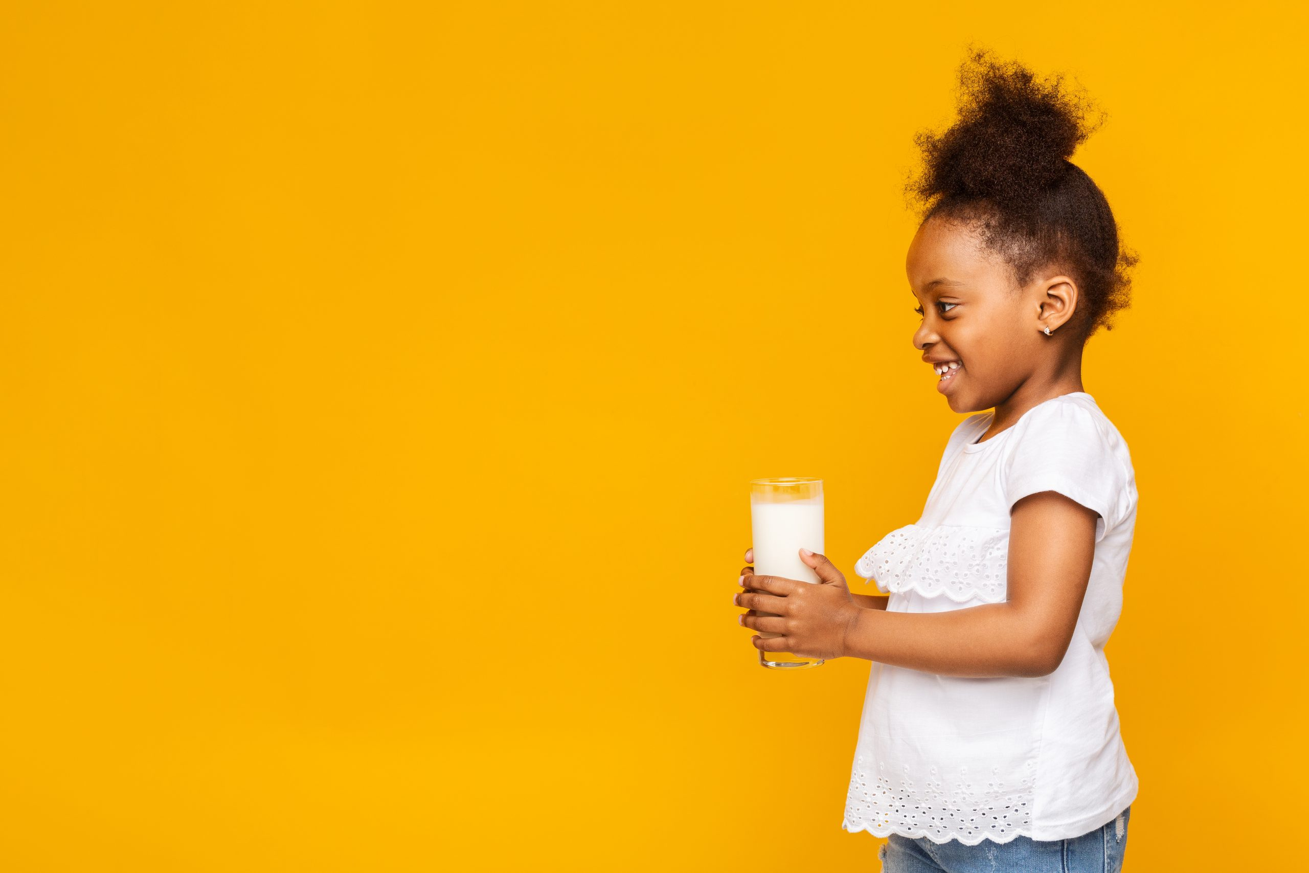 Adorable little african girl holding glass with fresh milk